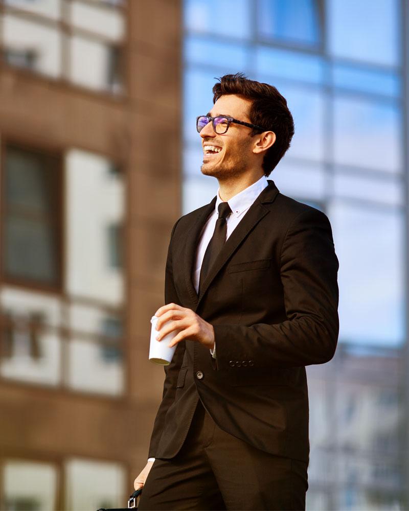 jeune professionnel à l'extérieur avec un café, l'air satisfait   PEHPP - Benoît Jacques